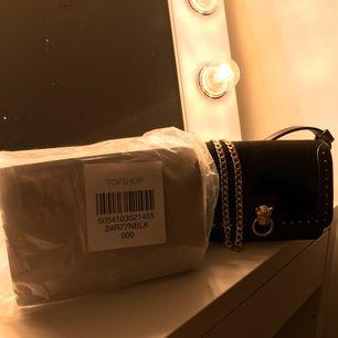 Helt ny inslagen väska från Topshop med snygga guld detaljer med en tiger i mitten, i precis samma modell som den till höger om den oöppnade. Råkade klicka hem 2 utav samma väska hihi så säljes för nypris.