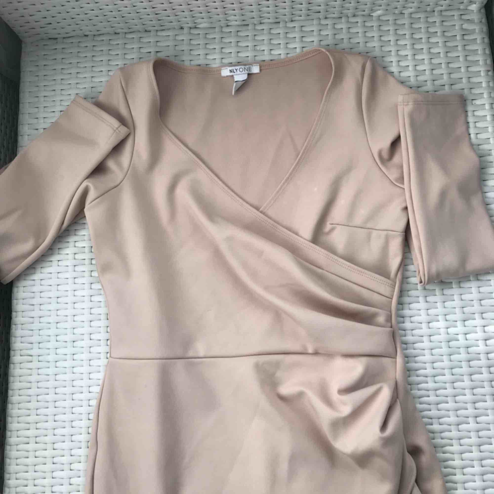 Jättefin klänning från Nelly.com använd endast en gång på ett bröllop, den räcker strax ovanför knä se bild :) du står för frakt! . Klänningar.