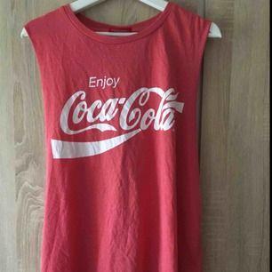 Ett koral färgat långt linne från Coca-Cola. Strl är 18år men passar nog de flesta. Den är öppen i ryggen. Fint skick. 25kr