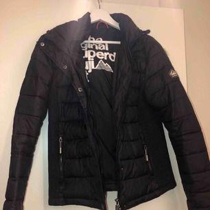 En svart superdry vinterjacka i storlek XL (små i storlekarna, är som en M). Väldigt snygg och varm jacka som tyvärr inte passar mig längre. Den är i nyskick och är köpt i deras egna butik i Stockholm.