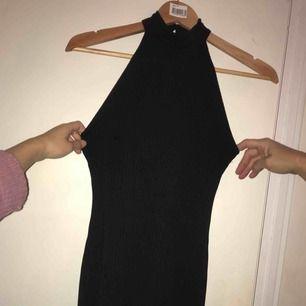 Frakt ingår i priset. Svart ribbad halterneckklänning med slits.