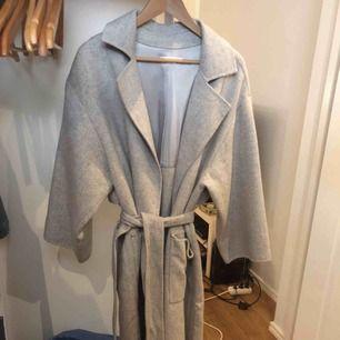 Jättefin grå kappa att använda till höst/vinter, köpt för ett år sen, aldrig använd. Finns både rep att knyta runt midjan och knappar.