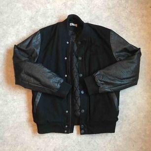 svart varsityjacka med läderdetaljer på ärmar och fickor.  Har ett hål i ena fickan, annars i fint skick!  Frakt tillkommer