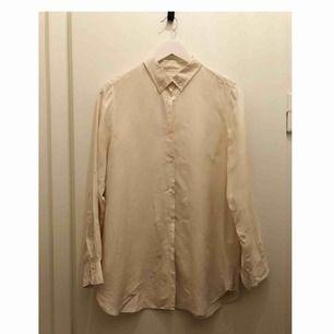Sidenskjorta från Filippa K i benvitt/cremefärg, längre modell. Har ett litet hål på ärmen men inget som märks, annars i fint skick :)