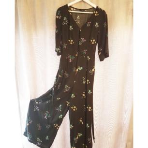 Underbar jumpsuit från Monki i härligt blommigt mönster. Den har knäppning fram och band i midjan! Möts upp i GBG eller fraktar mot 50kr.
