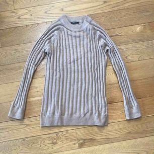 Beige glesstickad tröja från Gina Tricot. Tunn och praktisk att ha under tighta plagg eller små jackor på höst/vinter. Går mer över rumpan.