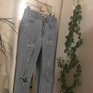 Ljusblåa mom jeans med slitningar från H&M. Frakt ingår inte i priset