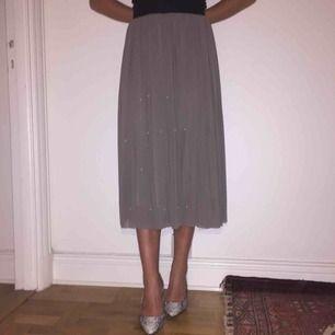 Vacker grå kjol med vita pärlor på. Plisserad och med ett jättefint fall på kjolen. Svart resårband i midjan så den passar alla storlekar. Köpt i London och är i superfint skick.