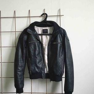 """Svart bikerjacka i """"skinn"""" från Lindex med dragkedjor i silver. Fint skick! :) fraktar och möts upp."""