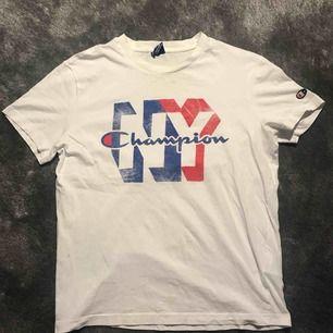 Gin T-shirt från champion. Tröjan är i bra skick förut några små hål vid halsen. Inget som syns när man har den på sig. Köparen står för frakt.