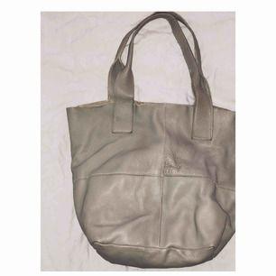Skinnväska i måtten höjd ca.36cm brädd ca.42cm och  Djup ca.20 cm - oanvänd! Kommer tillhörande plånboksficka. Handtagen passar perfekt över axeln. Väskan är köpt i Italien och märket är okänt.