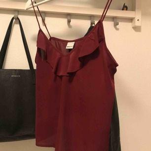 Vinrött linne från Gina tricot med spagetti straps. Kan fraktas för 15 kronor.