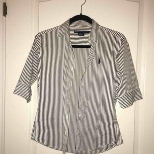 Kortärmad vit skjorta med mörkt marinblåa ränder i 100% bomull från Ralph Lauren. Endast använd en gång. Storlek 8 men passar för XS/S då den är lite liten i storlek. Möts upp i Stockholm. Frakt kan tillkomma.