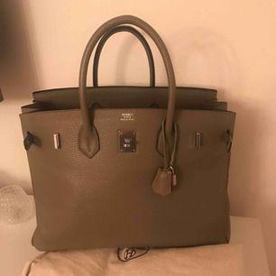 Elegant och snygg Birkin i grå/brun färg med silveriga detaljer. Lås, nyckel och dustbag ingår. Äkta skinn Frakt ingår i priset.