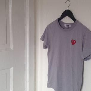 Superfin & najs grå Comme des garcons PLAY t-shirt. Äkta, köpt i PLAY-butik i Japan. Bra skick, knappt använd! Storlek M men CDGs storlekar är små så tänk typ mer S, men kan passa en M:) 895kr nypris