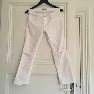 Vita stretch jeans m två hål på knänena och lite fransiga nertill, låg midja.