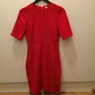 Figursydd klänning från H&M i jättefin röd nyans. Storlek 36. Aldrig använd då den tyvärr inte passar mig. Tight men inte super bodycon-tight, så väldigt bekväm! Har en fin smal cut-out i ryggen. Möts upp i centrala Stockholm, annars 49 kr frakt.