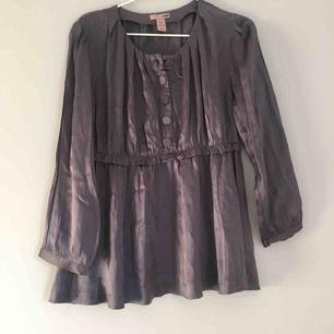 Jättefin grå blus från H&M i storlek 42 i 100% SIDEN.  Perfekt för både vardag och fest.