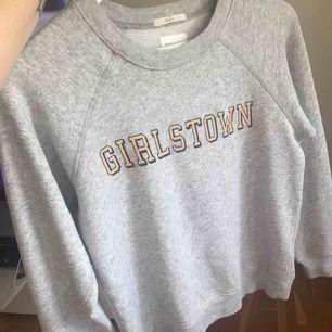 Grå collegetröja från Gant med texten 'girlstown', kan fraktas för 55 kronor!