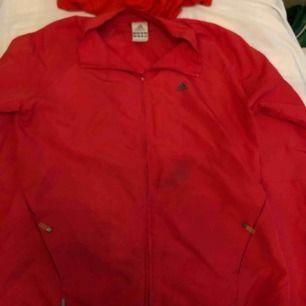 Adidas jacka i rött. En fläck på framsidan av jackan annars i bra skick. Frakt ingår
