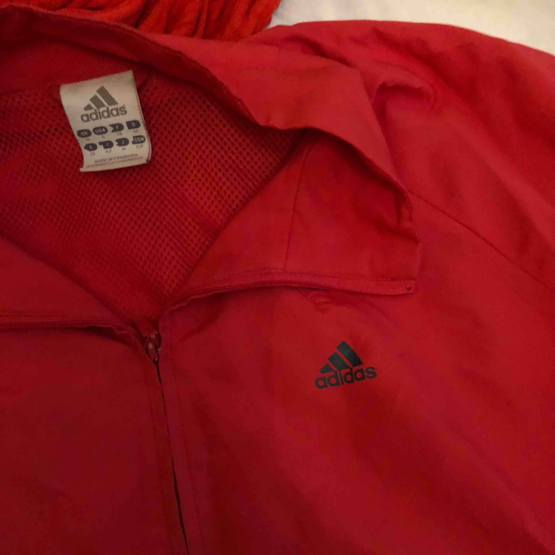 Adidas jacka i rött. En fläck på framsidan av jackan annars i bra skick. Frakt ingår. Jackor.