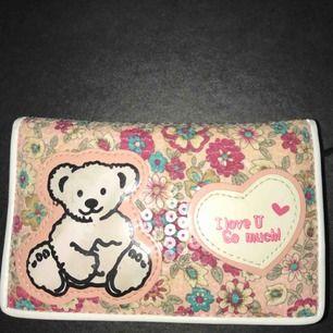 Säljer en sparsam plånbok med många kortfack och en annan fack med dragkedja som man kan lägga sina kontanter. Babyrosa med en liten björn på. Om ni har fler frågor skriv gärna!