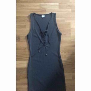 Mörkgrå klänning med snörning. Storlek M,