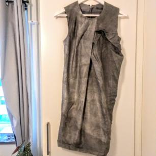 Löst sittande klänning från Cos som är veckad framtill. Skimrar i olika grå nyanser. Stängs med dragkedja längs ryggraden. Aldrig använd, tyvärr fel storlek.