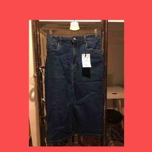 Lång oanvänd kjol med slits i mitten. Jeansmaterial från Lefties köpt i Barcelona. Prislappen är kvar. Storlek L men stretchig i midjan så passar mindre storlekar.