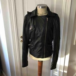 Exklusiv läderjacka (bikerjacket) med tyg hoodie som man kan ta av om man vill.  gjort av lammläder, mycket skön och mjuk. Välanvänd men fortfarande i bra skick.