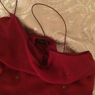 Röd klänning med tunna straps och broderade blommor i guld/brons. Står ingen storlek men skulle säga att den är S men är ganska kort. Möts upp eller skickar mot frakt