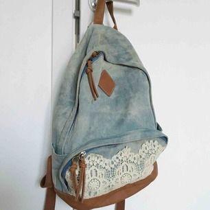 En ryggsäck i distressed jeans tyg, spets och konstgjord läder på botten. I normal storlek. Finns fickor på sidorna, stor öppning med en innerficka och ytterficka med spets som syns på bilderna.