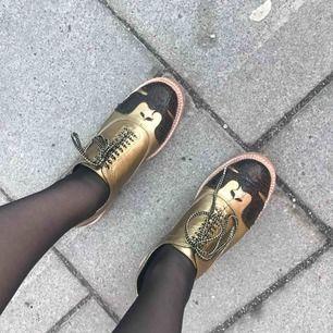 Moderna snygga skor från Chanel. Välgjord kopia i guld. Mes svarta detaljer. Fler bilder går att få. Frakt 70kr