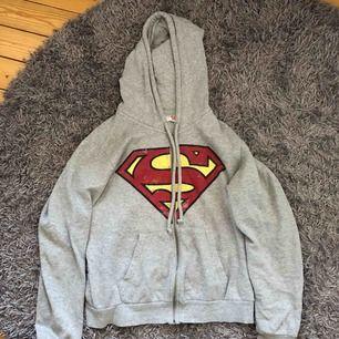 En grå luvtröja med dragkedja, superman tryck.  Bra skick, märket ska se slitet ut.  Köpare står för frakt.