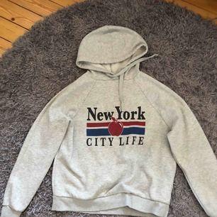 Grå hoodie med tryck, lappen är avklippt. Köpare står för frakt.