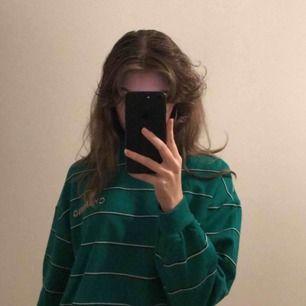 Ein BERSHKA CHARMING grüner Pullover mit rosa Text, einmal verwendet.