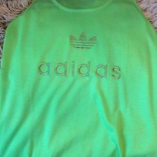 Adidas linne i trendig neongrön färg med broderad logga fram. Passar xs-m beroende på hur man vill att den sitter. Väldigt skönt material men jag är mer för neutrala färger ^^  Frakt står köparen för