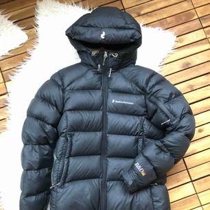Svart Peak Performance frost down jacket, använd en säsong, finns en liten lagning (se bild 2) som enligt mig inte alls syns när den är på. Annars toppenskick! Har mycket kvar att ge. Inköpt för 3795kr