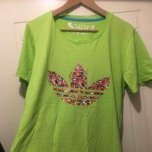 Adidas tshirt men inte älta. Märket gjord av flaggor vilket man inte ser ofta för adidas märket Trendig färg! Neon