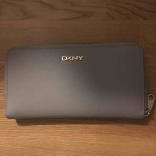 Buda på. Äkta  DKNY plånbok i super fint skick. Man kan få plats med mobilen, kort, kontanter och en massa mynt. Det enda är att guldfärgen på bokstäverna på framsidan har börjat gå bort lite men den är lika fon ändå!