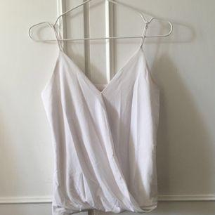 Fräscht vitt linne i kostym liknande material. V-ringad, justerbara axelband. Tyget går snett över magen. Finns även i svart. Frakt tillkommer💞