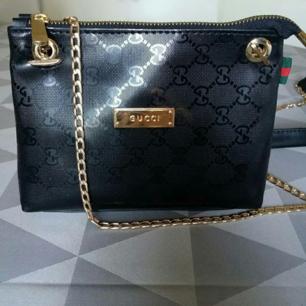 En väldigt fin liten axelremsväska (fejk Gucci) i svart. Mjuk sammetmaterial på insidan. Den är använd bara en gång så mycket fint skick. Köparen står för frakten.