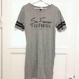 Grå t-shirt klänning med svart text. Använd 1 gång så jätte fint skick! Kan mötas upp i Stockholmsområdet.