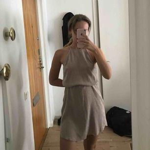 Oanvänd klänning i superfint material!!! Ljus lila/beige, svår färg att definiera men så fin verkligen. Den har inget skärp i midjan men jag skulle sätta ett skärp/snörning där. Eller så bär man den rak :)
