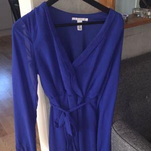 Fin blå klänning från Nelly, använd endast en gång, knyte runt midjan