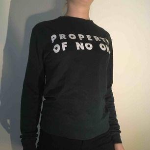 Mörkgrön tröja från H&M DIVIDED med vit text och muddar nertill. Texten lyder: PROPERTY OF NO ONE.  Tröjan är endast använd en gång, och texten  är inte sliten.   Frakt ingår ej i priset