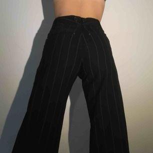 Svarta vit-randiga byxor, raka och vida (tajtare upptill). Passar säkert på någon med storlek 36. Det finns sammanlagt 8 knappar upptill på byxorna. Byxorna har ett hål i sidan av ena fickan men de är igen sytt och syns inte.