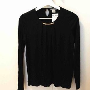 Svart långärmad tröja med gulddetalj vid halsen. Helt ny med prislappen kvar! Kan mötas upp i Stockholmsområdet eller frakta.