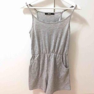 Grå jumpsuit med fickor och justerbara band. Superfint skick då den aldrig är använd. Kan mötas upp i Stockholmsområdet eller frakta.
