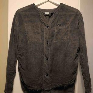 Tuff grå skjorta/blus från Crocker. Modell med slitna sömmar i kanterna. Lite längre bak. Öppna slitsar i sidorna. Ärmarna är aningen korta. Passar XS-S. Nypris 299kr